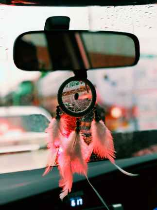 black and pink dreamcatcher hangs on vehicle rear mirror